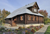 Beautiful wooden house with flowers, autumn — Stock Photo