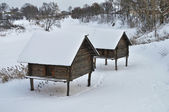 Barns on stilts at riverbank in winter — Stock Photo