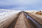 Asphalt road with dirty snow in early spring — Stock Photo