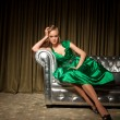 Girl in green dress sitting on couch — Stock Photo