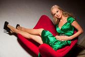 Blond elegante meisje, zittend op rode stoel — Stockfoto
