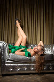 Girl in green dress laying on couch — Stock Photo