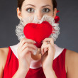 Shocked girl holding heart — Stock Photo