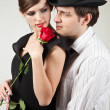 Young couple and red rose — Stock Photo