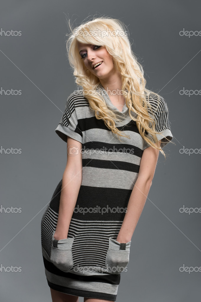 Beautiful blonde young woman in striped dress Studio shot on a grey background       — Stock Photo #5216632