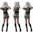 Tree girls holding happy and sad face masks symbolizing changing - Foto Stock