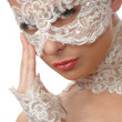 Beautiful woman with tender face in lace mask over her eyes - Stock Photo