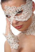 Beautiful woman with tender face in lace mask over her eyes — Stock Photo