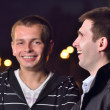 Two friends laughing at night city street — Stock Photo