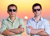 Dos amigos al atardecer lleva gafas de sol cruza sus brazos — Foto de Stock
