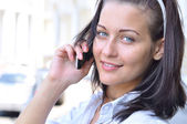 Krásná usměvavá žena mluví telefon na slunečné ulici — Stock fotografie