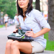 Young woman is closing laptop after work at city park — Stock Photo