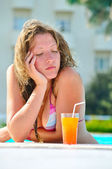 Sad pretty bored woman is sleeping in the hotel swimming pool — Stock Photo
