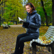Royalty-Free Stock Photo: Young woman is sitting on a bench in an autumn park and reading