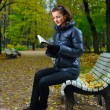 Young woman is sitting on a bench in an autumn park and reading — Stock Photo #4097976