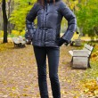 Young woman is standing at autumn park — Stock Photo