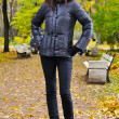 jonge vrouw is permanent in herfst park — Stockfoto