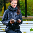 Young woman is sitting on a bench in an autumn park and reading — Stock Photo #4097992