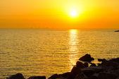 Sunrise in sea with city on skyline — Fotografia Stock