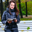Beautiful woman is sitiing in park and reading — Foto de Stock