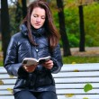 Beautiful woman is sitiing in park and reading — Stock Photo