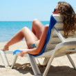 Stock Photo: Sexy woman is lying on chaise longue near a sea, view from behin
