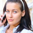 Beautiful smiling woman is talking phone at sunny street — Stock Photo