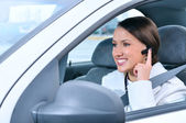 Beautiful woman is safely talking phone in a car using a bluetoo — Stock Photo