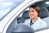 Mulher de negócios feliz num carro está olhando para a câmera — Foto Stock