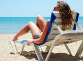Sexy woman is lying on chaise longue near a sea, view from behin — Stock Photo