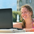 Woman is using laptop from swimming pool near the hotel — Stock Photo #4198974
