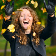 Happy woman is throwing dry autumn leaves in park — Stock Photo #4198978
