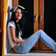 Pretty woman is sitting on window with book on head — Stock Photo #4199002