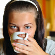 young woman is drinking coffee in cafe and looking at camera — Stock Photo