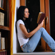 Pretty woman is sitting on window and reading book — Stock Photo #4199005
