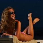 Happy woman is lying on the night beach — Stock Photo