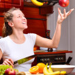 Happy woman is cooking fruit salad out of flying fruits - Stock Photo