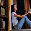 Pretty woman is sitting on window and dreaming — Stock Photo