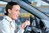 Happy business woman in a car is looking at camera — Stockfoto