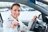 Happy woman is showing keys of her new car — Stock Photo