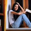 Beautiful woman is sitting on a windowsill and holding a book — Stock Photo