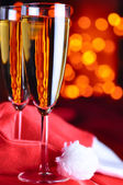 Two champagne glasses on red silk — Stock Photo