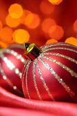 Christmas decorative balls on red silk against blurred lights on — Stock fotografie