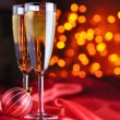 Foto Stock: Two champagne glasses on red silk