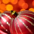 Christmas decorative balls on red silk against blurred lights on — Stock Photo