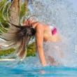 Slim woman is spectacularly jumping out of pool and shaking hair — Stock Photo