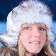 Royalty-Free Stock Photo: Beautiful young woman in furry hat at winter evening