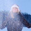Foto Stock: Woman is throwing snow at winter evening