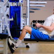 Young handsome man is training in gym using a rower — Стоковая фотография