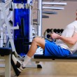 Young handsome mis training in gym using rower — Stockfoto #4350694